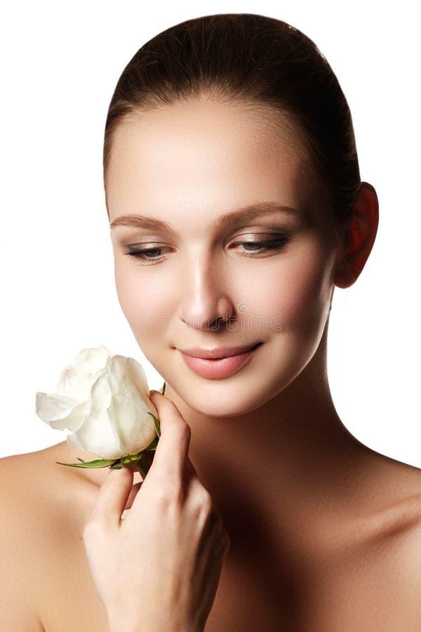 Hübsches Gesicht der schönen jungen Frau mit stieg auf Hände - Weiß lizenzfreie stockfotos