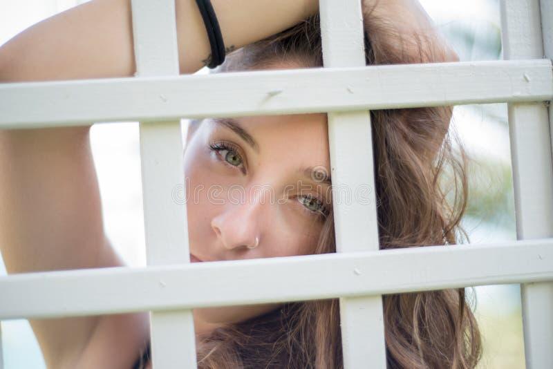 Hübsches Gesicht einer Dame, welche hinten die Kamera eines hölzernen Gitters schaut lizenzfreies stockfoto