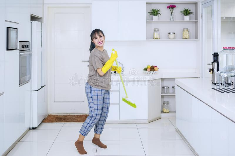Hübsches Haushälterintanzen mit einem Besen in der Küche lizenzfreie stockfotografie