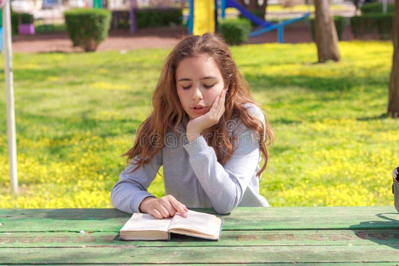 Hübsches Jugendlichmädchen, das ein Buch liest und Hausarbeit am Sommerpark studiert stockfoto