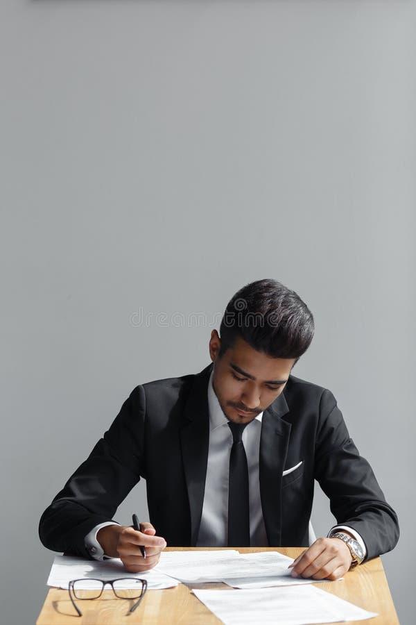 Hübsches junges Geschäftsmannschreiben, der Geschäftsmann, der mit Dokumenten arbeitet, erkennen den Vertrag an und sitzen am Sch stockfoto