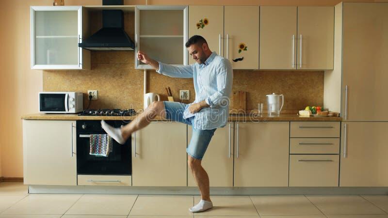 Hübsches junges lustiges Manntanzen in der Küche zu Hause morgens und haben Spaß an den Feiertagen lizenzfreies stockfoto