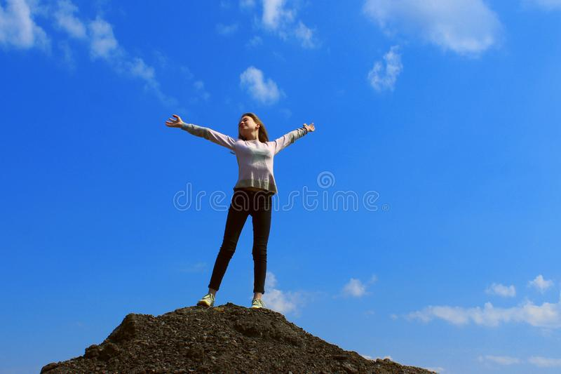 H?bsches junges M?dchen, das auf die Oberseite des Berges und des H?ndchenhaltens oben ?ber blauer Himmel-Hintergrund steht lizenzfreie stockbilder