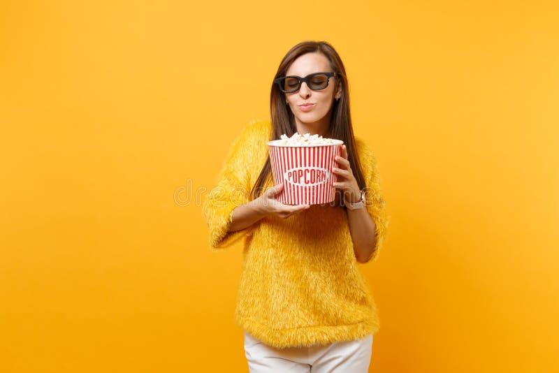 Hübsches junges Mädchen in imax 3d Gläsern Film, Holdingeimer, Schnüffelnpopcorn aufpassend lokalisiert auf hellem Gelb stockfoto