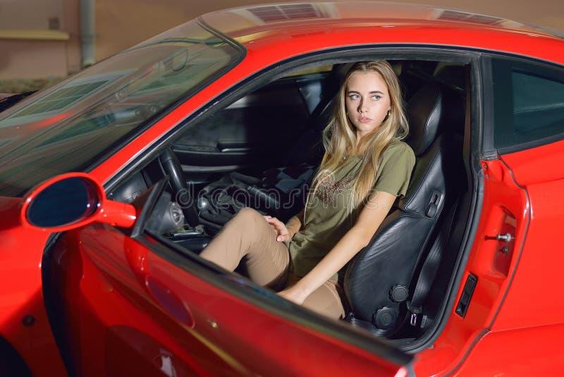 Hübsches junges Mädchen sitzt hinter dem Rad stockfoto
