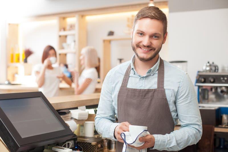 Hübsches junges männliches barista wäscht Tonware herein lizenzfreies stockbild