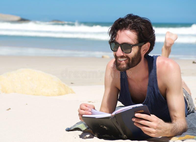 Hübsches junges Mannlächeln und -lesebuch auf dem Strand lizenzfreie stockbilder