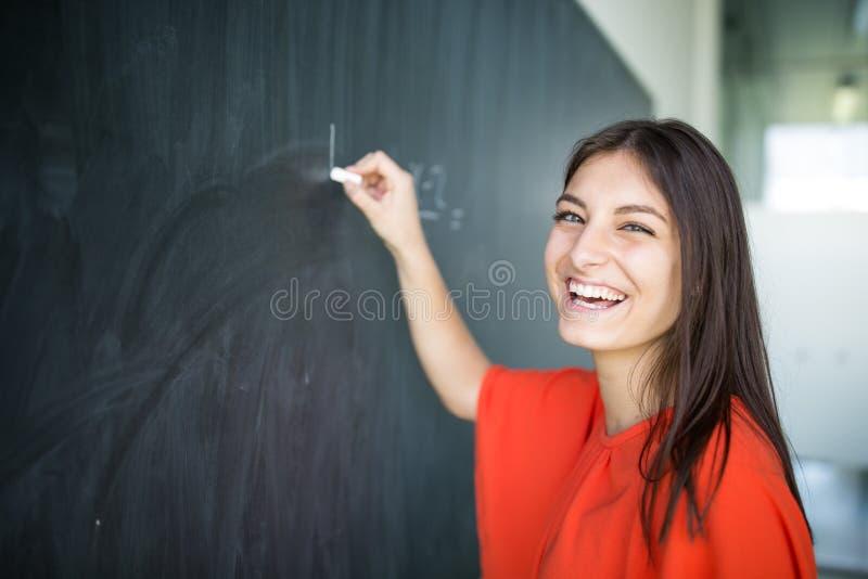 Hübsches, junges Studentschreiben auf der Tafel lizenzfreies stockfoto