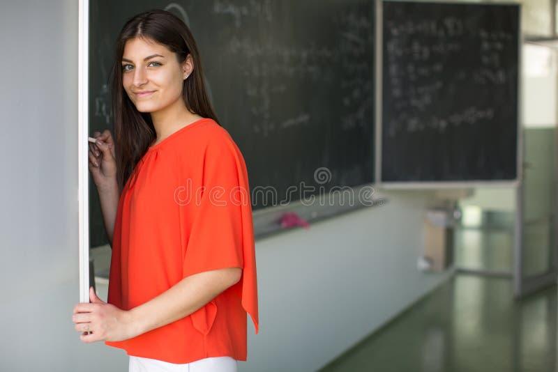 Hübsches, junges Studentschreiben auf der Tafel lizenzfreies stockbild