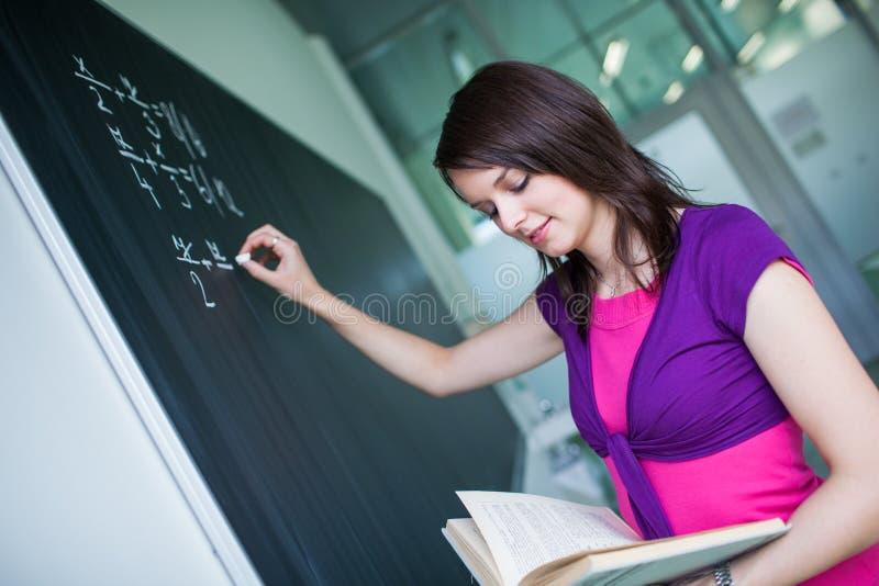 Hübsches, junges Studentschreiben auf der Tafel/dem blackboa lizenzfreies stockbild