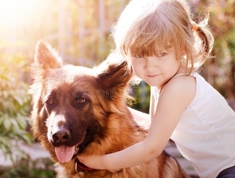 Hübsches kleines Mädchen, ihren flaumigen Freund umarmend, Schäferhundhund lizenzfreies stockbild