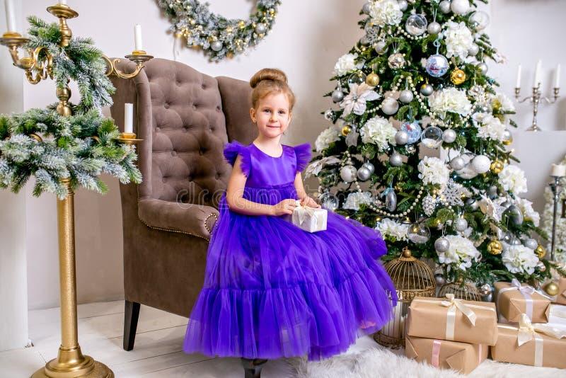 Hübsches kleines Mädchen 4 Jahre alt in einem blauen Kleid Baby im Weihnachtsraum mit teddybear, großer Uhr, Weihnachtsbaum, brau stockbild