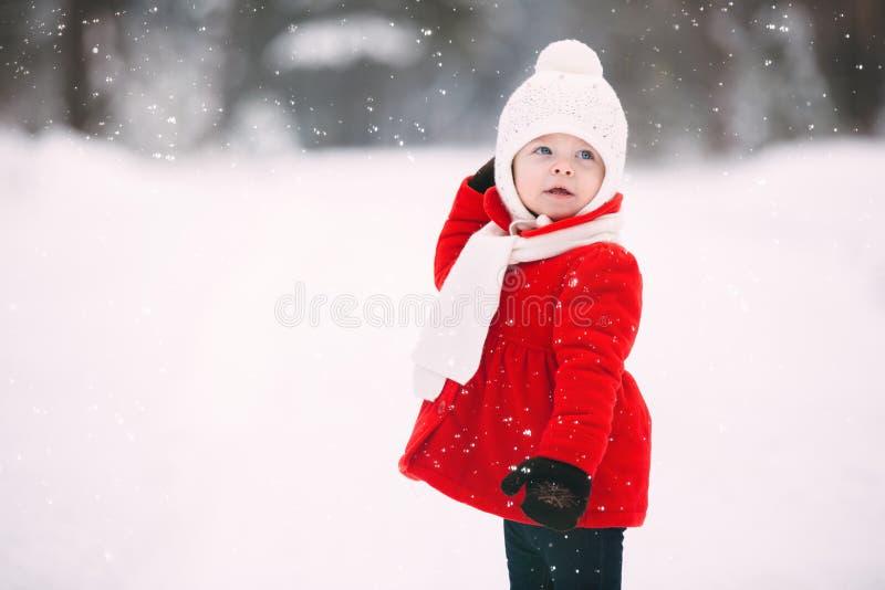 Hübsches kleines Mädchen in rotem Mantel im Winter Wald fröhliches kleines Mädchen in Handschuhen und weißer Hut auf schneeweiß stockfotografie