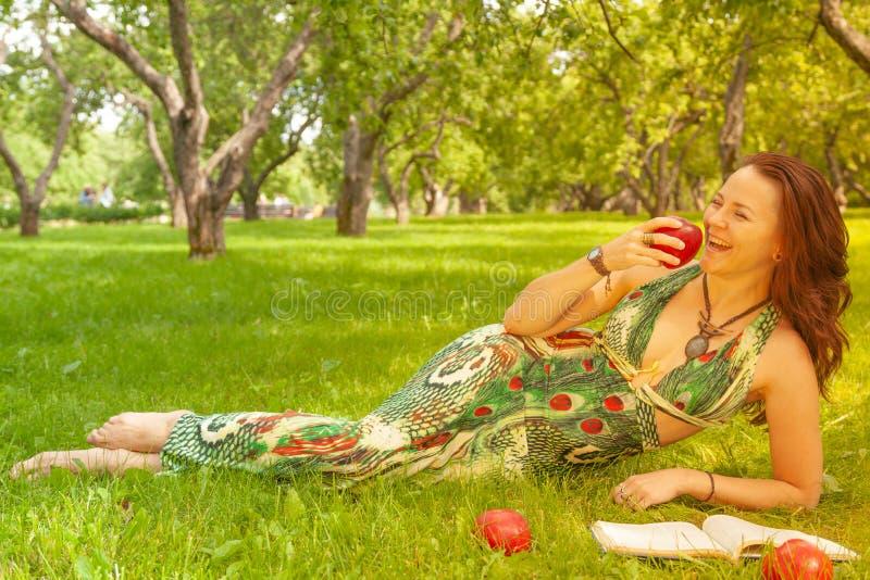 Hübsches lächelndes glückliches Mädchen im grünen Kleiderlesebuch und Lügen auf dem Gras lizenzfreie stockfotos