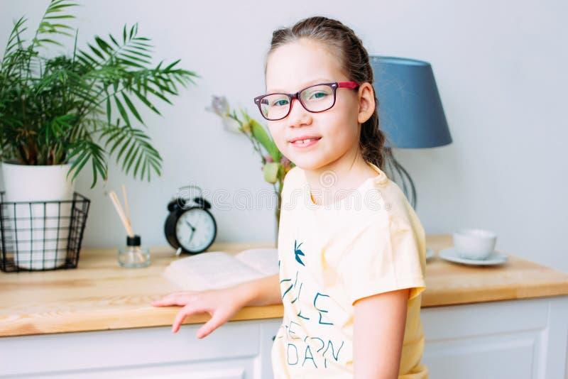 Hübsches lächelndes kleines Mädchen in den Gläsern und in Zöpfen, die mit Buch am Tisch in ihrem Raum sitzen lizenzfreie stockbilder
