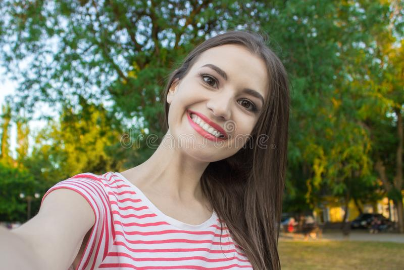 Hübsches lächelndes Mädchen, das selfie, langhaarigen Brunette in der weißen Kleidung, Nahaufnahme macht lizenzfreie stockbilder