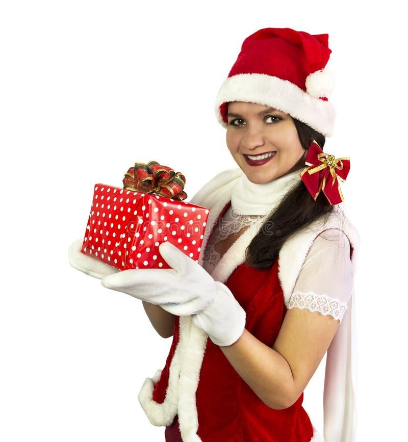 Hübsches lächelndes Mädchen in rotem Sankt-Kostüm mit Geschenk stockfotografie