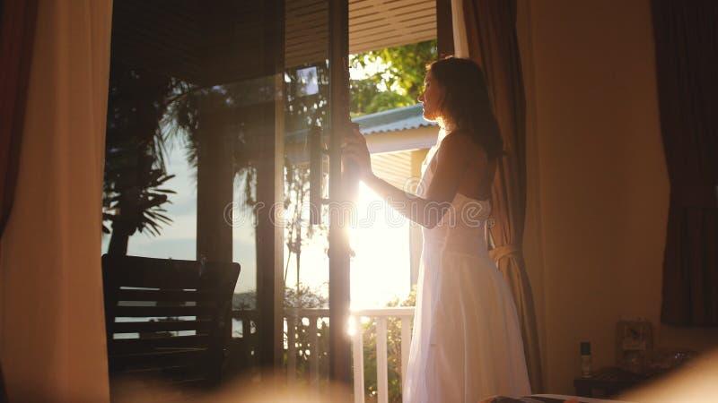 Hübsches Mädchen öffnet die Tür am frühen Morgen während des Sonnenaufgangs mit Blendenfleckeffekten und geht zur Terrasse heraus stockfoto