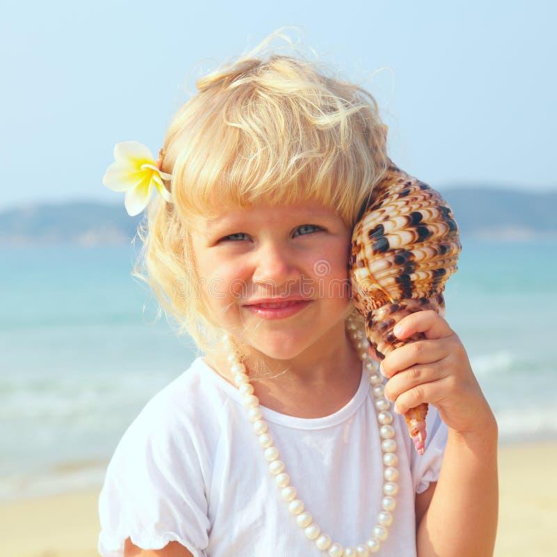 Hübsches Mädchen auf dem Strand mit Seashell lizenzfreie stockfotografie