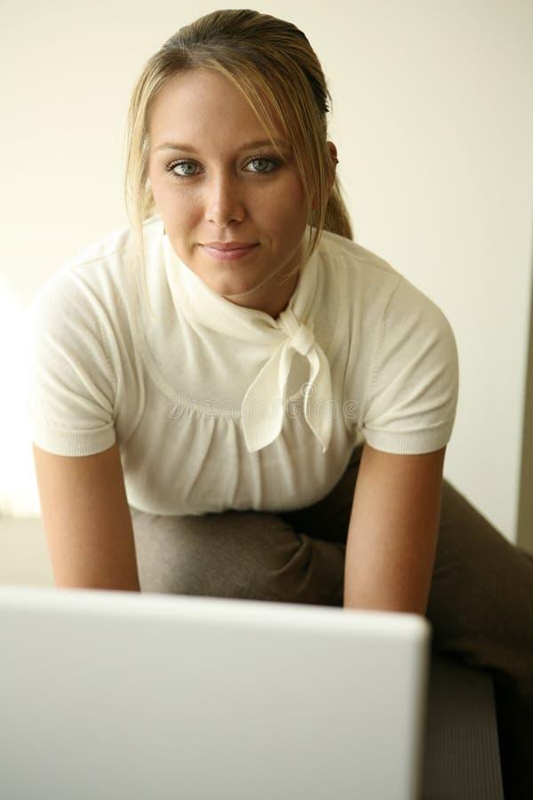 Hübsches Mädchen, das über Computer schaut lizenzfreies stockbild