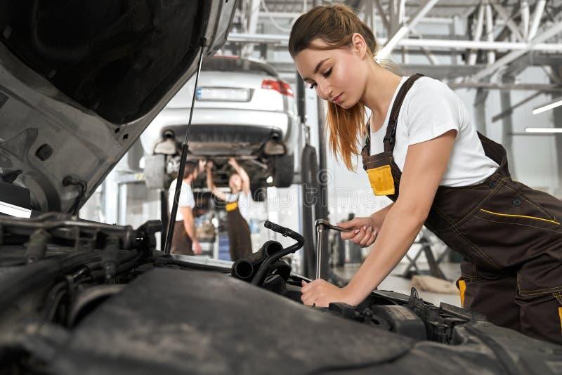 Hübsches Mädchen, das als Mechaniker im autoservice arbeitet lizenzfreies stockbild