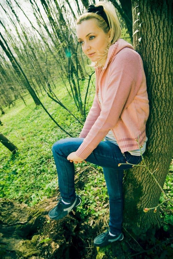 Hübsches Mädchen, das auf Baum sich lehnt stockbild