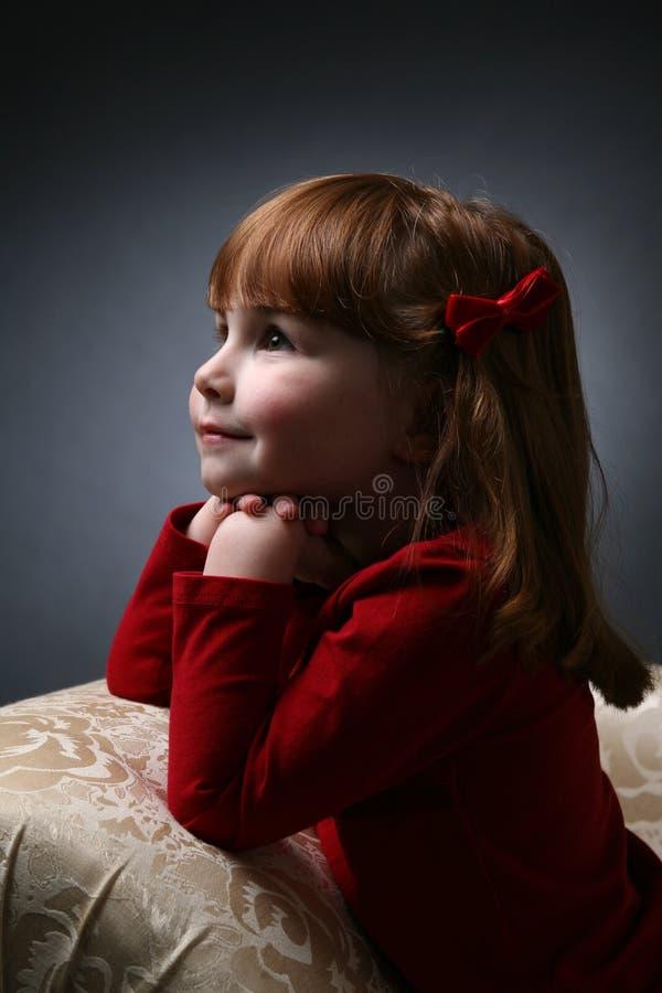Hübsches Mädchen, das auf Couch mit dem Kinn auf Händen knit stockfotografie