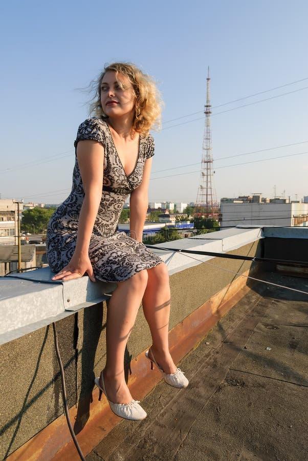 Hübsches Mädchen, das auf Dach sitzt stockfotos