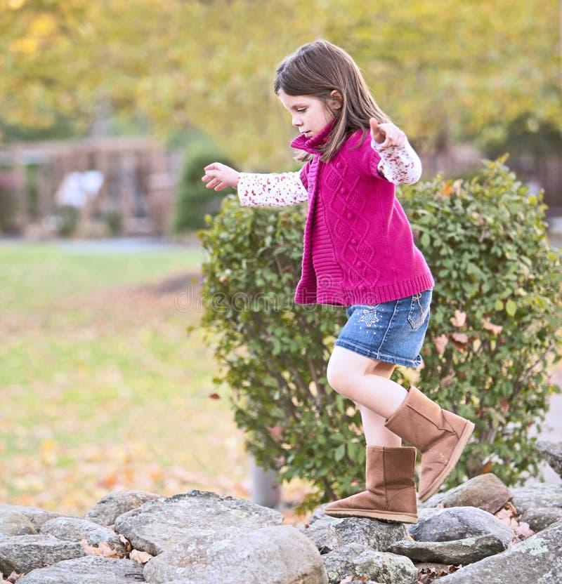 Hübsches Mädchen, das auf den Felsen klettert stockbild