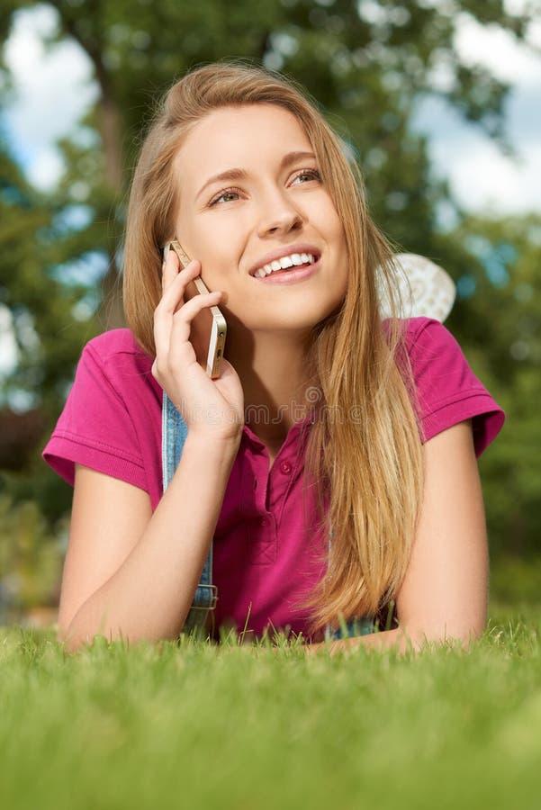 Hübsches Mädchen, das auf ihrem Mobiltelefon liegt im Stadtpark spricht lizenzfreies stockbild