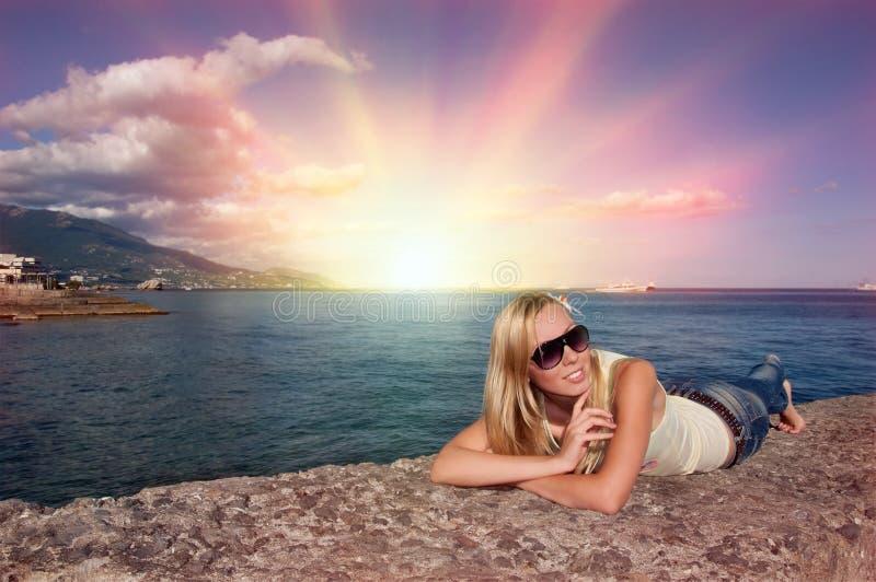 Hübsches Mädchen, das auf Landungstufe liegt und sich entspannt stockbilder