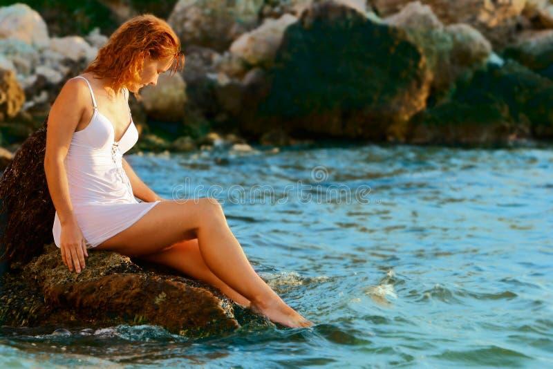 Hübsches Mädchen, das auf Stein sitzt lizenzfreie stockbilder