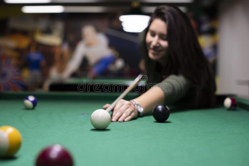 Hübsches Mädchen, das Billard spielt lizenzfreie stockfotografie