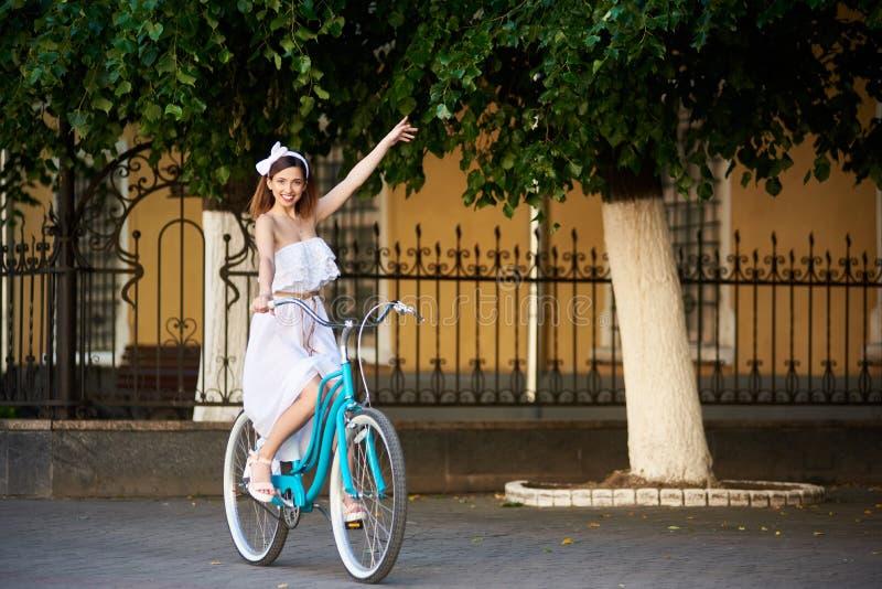 Hübsches Mädchen, das blaues Fahrrad reitet und Hand wellenartig bewegt stockfotos
