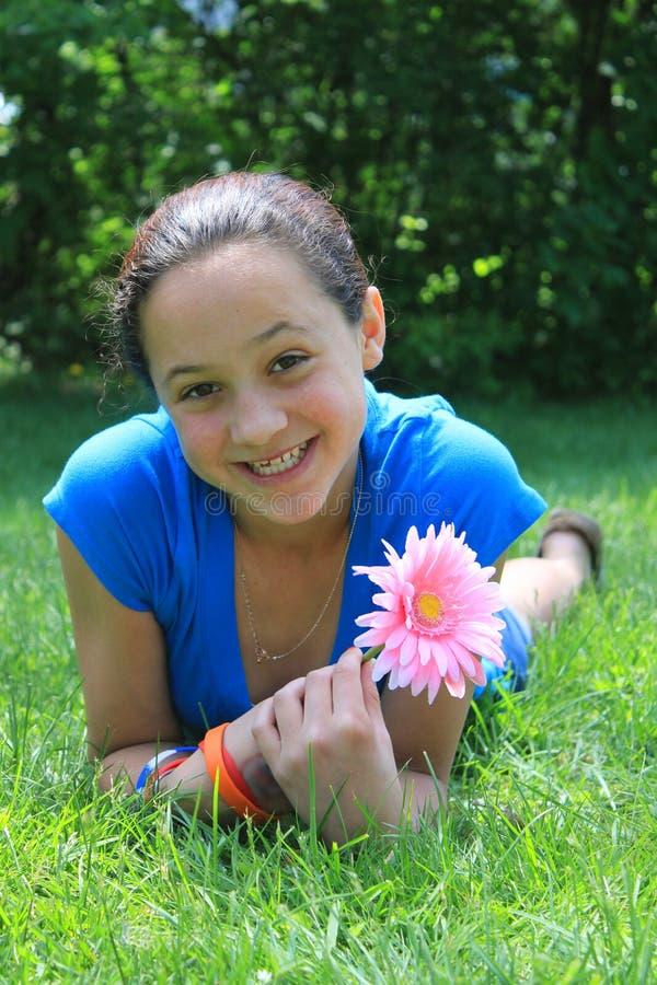 Hübsches Mädchen, das eine Blume anhält stockbilder