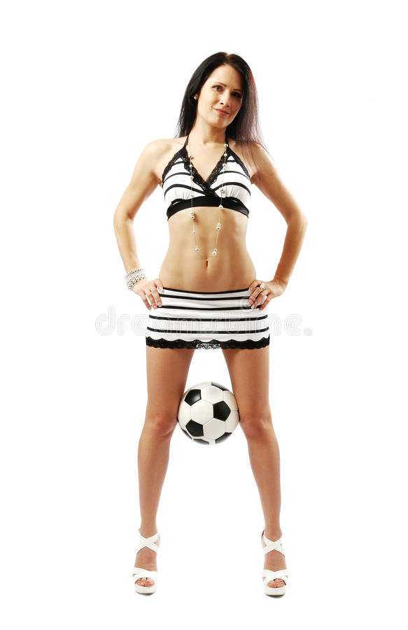Hübsches Mädchen, das einen Fußball zwischen ihren Fahrwerkbeinen anhält stockfotos