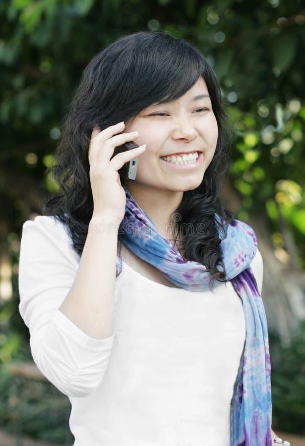 Hübsches Mädchen, das einen Handy verwendet stockfotografie