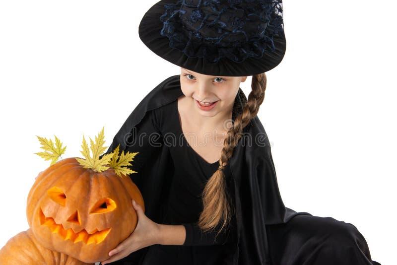 Hübsches Mädchen, das einen Kürbis hält Halloween lizenzfreie stockbilder