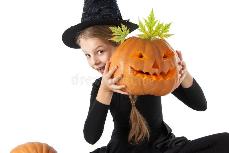 Hübsches Mädchen, das einen Kürbis hält Halloween stockfotografie