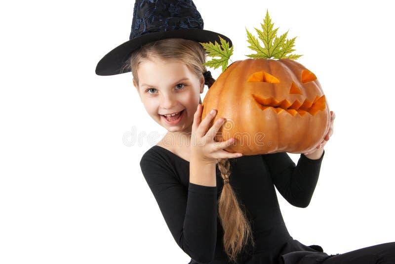 Hübsches Mädchen, das einen Kürbis hält Halloween lizenzfreie stockfotos
