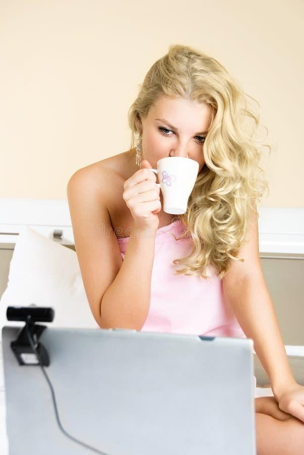 Hübsches Mädchen, das einen Laptop mit einer Web-Kamera verwendet stockbilder