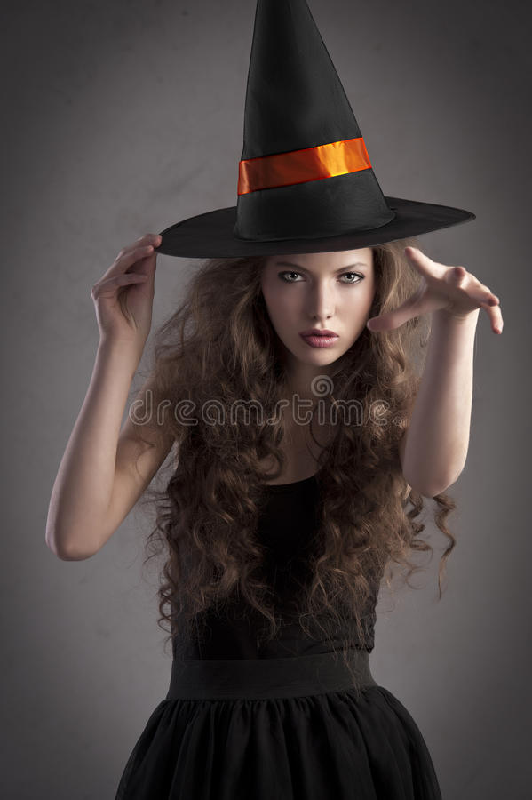 Hübsches Mädchen, das einen sehr großen Hexehut trägt stockfoto