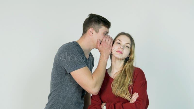 Hübsches Mädchen, das Geheimnis im Ohr ihres lachenden Freunds auf weißem Hintergrund - Freundschaftskonzept flüstert stockbilder