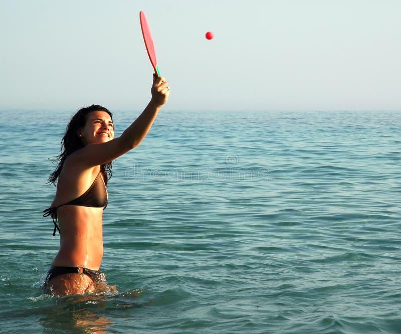 Hübsches Mädchen, das Kugel im Ozean spielt lizenzfreies stockbild
