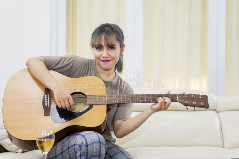 Hübsches Mädchen, das lernt, eine Akustikgitarre zu spielen lizenzfreies stockbild