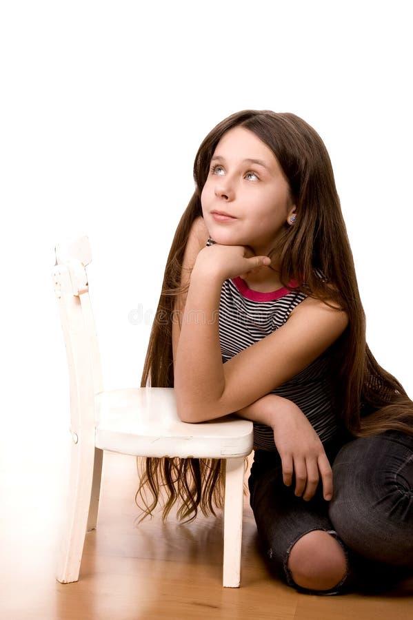 Hübsches Mädchen, das oben schaut und auf Weiß träumt lizenzfreies stockfoto