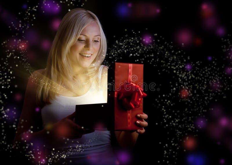 Hübsches Mädchen, das roten Weihnachtsgeschenkkasten öffnet stockfoto