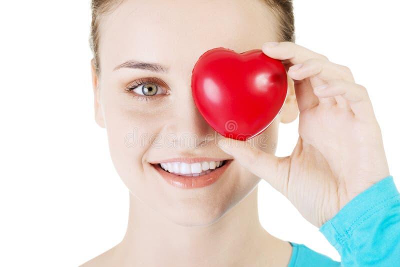 Hübsches Mädchen, das rotes Herz zeigt stockbild