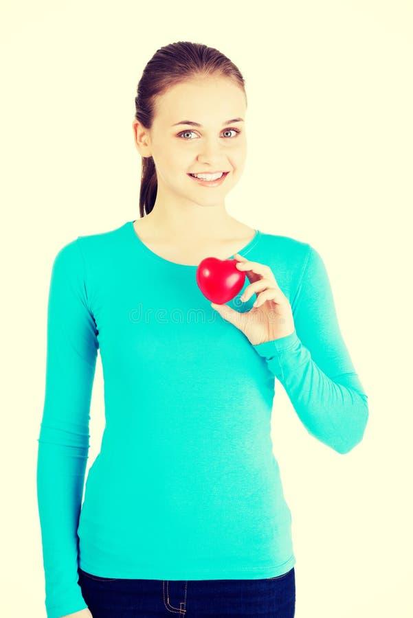 Hübsches Mädchen, das rotes Herz zeigt lizenzfreie stockfotos