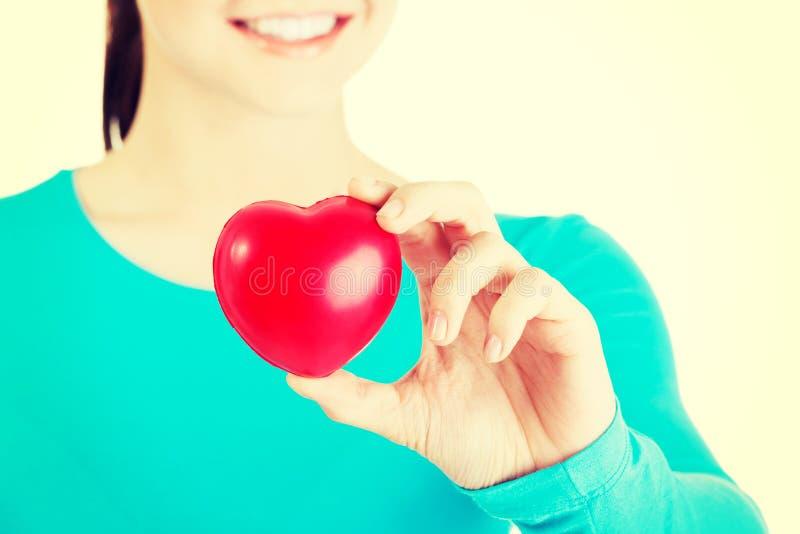 Hübsches Mädchen, das rotes Herz zeigt lizenzfreie stockfotografie